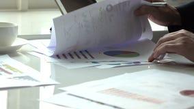 Εργασία επιχειρηματιών στην αρχή με το έγγραφο γραφικών παραστάσεων απόθεμα βίντεο