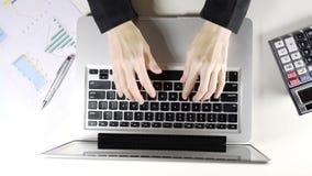 Εργασία επιχειρησιακών γυναικών στην αρχή με τη δακτυλογράφηση του φορητού προσωπικού υπολογιστή στον άσπρο πίνακα απόθεμα βίντεο