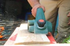 εργασία εργαλείων κλειδιών εξοπλισμού fow Ένα άτομο ξυλουργών βάζει μια ξύλινη σανίδα ενάντια σε ένα ε Στοκ φωτογραφία με δικαίωμα ελεύθερης χρήσης