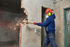 Εργασία και αναδιοργάνωση κατεδάφισης εργαζόμενος με τη βαρειά που καταστρέφει τον τοίχο στοκ εικόνα με δικαίωμα ελεύθερης χρήσης