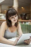 Εργασία κοριτσιών ομορφιάς για το PC ταμπλετών στο εσωτερικό στοκ εικόνα με δικαίωμα ελεύθερης χρήσης