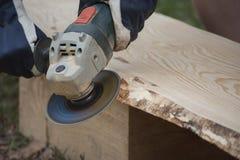Εργασία με τη μηχανή μύλων γωνίας και ξύλινη σανίδα από το πεύκο για το ανώτατο όριο σπιτιών κούτσουρων Στοκ εικόνα με δικαίωμα ελεύθερης χρήσης