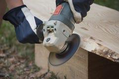 Εργασία με τη μηχανή μύλων γωνίας και ξύλινη σανίδα από το πεύκο για το ανώτατο όριο σπιτιών κούτσουρων Στοκ εικόνες με δικαίωμα ελεύθερης χρήσης