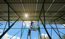 Εργασία ομάδας: οθόνη ηλιακών πλαισίων κατά τη διάρκεια εγκατάστασης θερινής της ηλιόλουστης ημέρας στοκ φωτογραφία