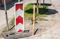 Εργασία σημαδιών οδικής κυκλοφορίας μπροστά με τα κόκκινα και άσπρα εμπόδια στο εργοτάξιο οικοδομής οδών στην πόλη Στοκ φωτογραφία με δικαίωμα ελεύθερης χρήσης