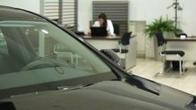Εργασία στην αίθουσα εκθέσεως Διευθυντής πωλήσεων στις εργασίες αντιπροσώπων σε ένα γραφείο Στο πρώτο πλάνο του αυτοκινήτου, ο δι φιλμ μικρού μήκους