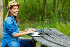 Εργασία στον κήπο με το φλυτζάνι lap-top και καφέ Στοκ Φωτογραφίες