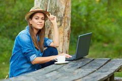 Εργασία στον κήπο με το φλυτζάνι lap-top και καφέ Στοκ φωτογραφία με δικαίωμα ελεύθερης χρήσης