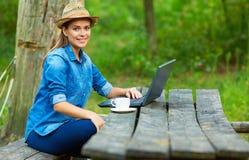 Εργασία στον κήπο με το φλυτζάνι lap-top και καφέ Στοκ εικόνα με δικαίωμα ελεύθερης χρήσης