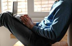 Εργασία στο lap-top Unrecognizable νεαρός άνδρας που δακτυλογραφεί κάτι στη συνεδρίαση lap-top του στο μπαλκόνι κοντά στο παράθυρ Στοκ φωτογραφία με δικαίωμα ελεύθερης χρήσης