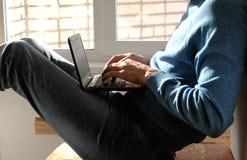 Εργασία στο lap-top Unrecognizable νεαρός άνδρας που δακτυλογραφεί κάτι στη συνεδρίαση lap-top του στο μπαλκόνι κοντά στο παράθυρ Στοκ Εικόνα