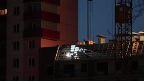 Εργασία συγκόλλησης για τη στέγη της πολυκατοικίας κάτω από την κατασκευή τη νύχτα φιλμ μικρού μήκους