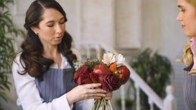 Εργασία τριών νέα όμορφη ανθοκόμων αρχιμαγείρων στο κατάστημα φρούτων λουλουδιών που κάνει την ανθοδέσμη φρούτων και λαχανικών απόθεμα βίντεο