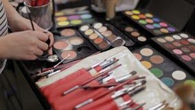 Εργασία των επαγγελματικών καλλυντικών καλλιτεχνών σύνθεσης στο σαλόνι σύνθεσης Πολυτελή καλλυντικά για τη σύνθεση πολύχρωμος απόθεμα βίντεο