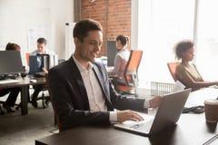 Εργασία υπαλλήλων χαμόγελου αρσενική με το έγγραφο σχετικά με το lap-top στοκ φωτογραφίες