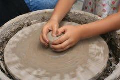 Εργασία χεριών παιδιών για τις ρόδες αγγειοπλαστών στοκ εικόνα