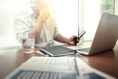 Εργασία χεριών σχεδιαστών και έξυπνο τηλέφωνο και lap-top στο ξύλινο γραφείο Στοκ Εικόνες