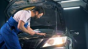 Εργασίες ατόμων με ένα lap-top σε ένα γκαράζ, πλάγια όψη Επισκευαστής που καθορίζει ένα αυτοκίνητο Έννοια υπηρεσιών αυτοκινήτων απόθεμα βίντεο