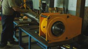 Εργασίες ατόμων στο εργοστάσιο με το φραγμό μετάλλων Ο μηχανικός ενεργοποιεί τη μηχανή, οι βοηθητικές βοήθειες κινούν προσεκτικά  απόθεμα βίντεο