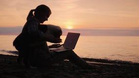 Εργασίες γυναικών blogger με ένα lap-top, αυτή που αποσπάται το κουτάβι της απόθεμα βίντεο