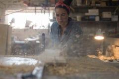 Εργασίες κοριτσιών ξυλουργών για ένα πριόνι και τα πριόνια ένα ξύλινο προϊόν στοκ φωτογραφίες