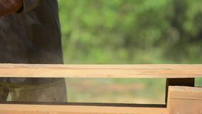 Εργασίες ξυλουργών με έναν ηλεκτρικό τρίφτη και ξύλινα προϊόντα διαδικασιών Ξυλουργός με το φορητό ηλεκτρικό τρίφτη στα χέρια στο απόθεμα βίντεο