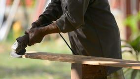 Εργασίες ξυλουργών με έναν ηλεκτρικό τρίφτη και ξύλινα προϊόντα διαδικασιών Ξυλουργός με το φορητό ηλεκτρικό τρίφτη στα χέρια στο φιλμ μικρού μήκους