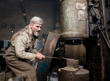 Εργασίες σιδηρουργών με ένα σφυρί δύναμης Στοκ εικόνα με δικαίωμα ελεύθερης χρήσης