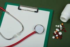 Εργασιακός χώρος γιατρών - κόκκινο στηθοσκόπιο, χάπια, ιατρικά μπουκάλια και ε Στοκ Εικόνα