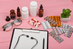 Εργασιακός χώρος γιατρών με την κενή περιοχή αποκομμάτων, τα μπουκάλια ιατρικής, το κόκκινο στηθοσκόπιο, eyeglasses και τα χάπια  στοκ φωτογραφία με δικαίωμα ελεύθερης χρήσης
