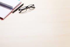 Εργασιακός χώρος γραφείων γραφείων με το σημειωματάριο και τα γυαλιά Στοκ Φωτογραφίες