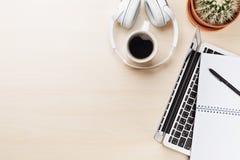 Εργασιακός χώρος γραφείων γραφείων με το lap-top, τον καφέ και τα ακουστικά Στοκ Φωτογραφία