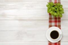 Εργασιακός χώρος γραφείων με πράσινο houseplant στο ελεγμένο τραπεζομάντιλο, φλιτζάνι του καφέ Στοκ εικόνα με δικαίωμα ελεύθερης χρήσης