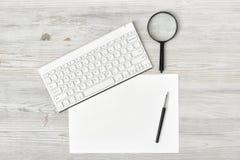 Εργασιακός χώρος γραφείων με το πληκτρολόγιο, μάνδρα, άσπρο κενό έγγραφο και πιό magnifier Στοκ Φωτογραφία