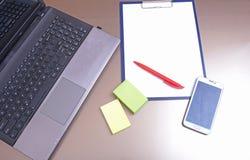 Εργασιακός χώρος γραφείων με το lap-top, έξυπνο τηλέφωνο στον πίνακα Στοκ εικόνα με δικαίωμα ελεύθερης χρήσης