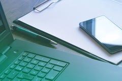Εργασιακός χώρος γραφείων με το lap-top, το έξυπνα τηλέφωνο και το φλυτζάνι καφέ στον πίνακα Στοκ Φωτογραφία