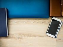 Εργασιακός χώρος γραφείων με το lap-top, το σημειωματάριο, το τηλέφωνο και τη μάνδρα στον ξύλινο πίνακα Στοκ Φωτογραφίες