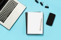 Εργασιακός χώρος με το ανοικτό lap-top, άσπρο και μαύρο εξάρτημα στον μπλε πίνακα Τοπ διάστημα άποψης και αντιγράφων στοκ εικόνα