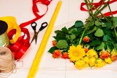 Εργασιακός χώρος του ανθοκόμου, που κάνει την ανθοδέσμη Κίτρινα και πορτοκαλιά τριαντάφυλλα επάνω Στοκ φωτογραφία με δικαίωμα ελεύθερης χρήσης
