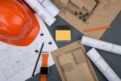 Εργασιακός χώρος του αρχιτέκτονα - κράνος, κατασκευαστικά σχέδια, ρολόι στοκ φωτογραφία