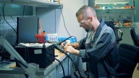 Εργαστήριο με έναν άνδρα υπάλληλος που συγκολλά ένα κύκλωμα με τα τεχνητά χέρια απόθεμα βίντεο