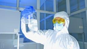 Εργαστήριο χημείας - επιστήμονας στο προστατευτικό κοστούμι που ελέγχει το μπουκάλι με τον αντιδραστικό πράκτορα απόθεμα βίντεο