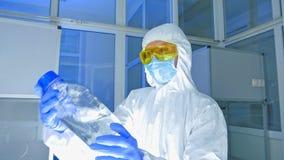 Εργαστήριο χημείας - επιστήμονας στο προστατευτικό μπουκάλι τινάγματος κοστουμιών με αντιδραστικό απόθεμα βίντεο