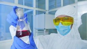 Εργαστήριο χημείας - ερευνητής που αναλύει ένα υγρό σε μια φιάλη απόθεμα βίντεο