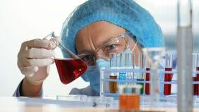 Εργαστήριο χημείας - ερευνητής που αναλύει ένα υγρό σε μια φιάλη φιλμ μικρού μήκους