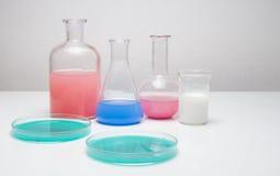 Εργαστηριακά γυαλικά με τα υγρά των διαφορετικών χρωμάτων Στοκ Φωτογραφία