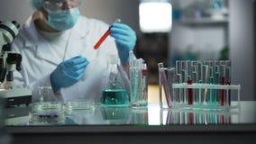 Εργαστηριακός βοηθός που εξετάζει το ιατρικό δείγμα αίματος που ψάχνει τα ιζήματα απόθεμα βίντεο