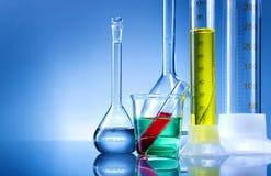 Εργαστηριακός εξοπλισμός, μπουκάλια, φιάλες με το υγρό χρώματος στο μπλε υπόβαθρο Στοκ Εικόνες