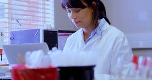 Εργαστηριακός τεχνικός που χρησιμοποιεί το lap-top στην τράπεζα αίματος 4k φιλμ μικρού μήκους