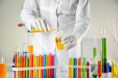 Εργαστηριακό βοηθητικό χύνοντας υγρό από το σωλήνα δοκιμής στη φιάλη πέρα από τον πίνακα στοκ εικόνες με δικαίωμα ελεύθερης χρήσης